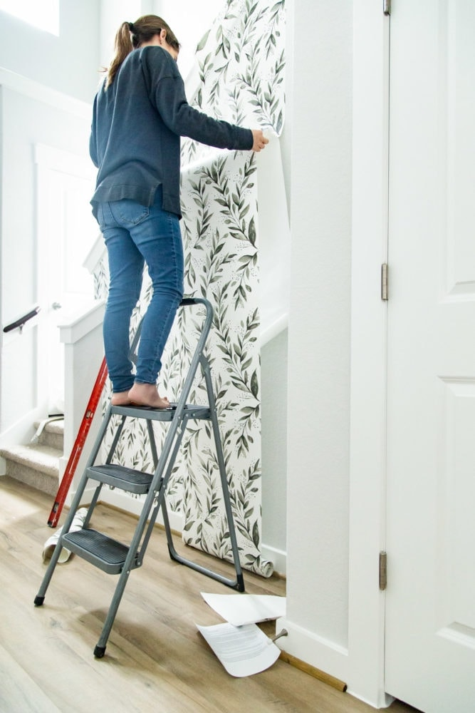 woman installing peel and stick wallpaper on textured walls
