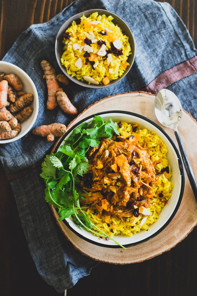 This Instant Pot coconut pork is cooked with turmeric, ginger, cinnamon and cardamom. It's aromatic, juicy and tender and perfect served over turmeric ginger rice with dried fruit and sliced almonds.