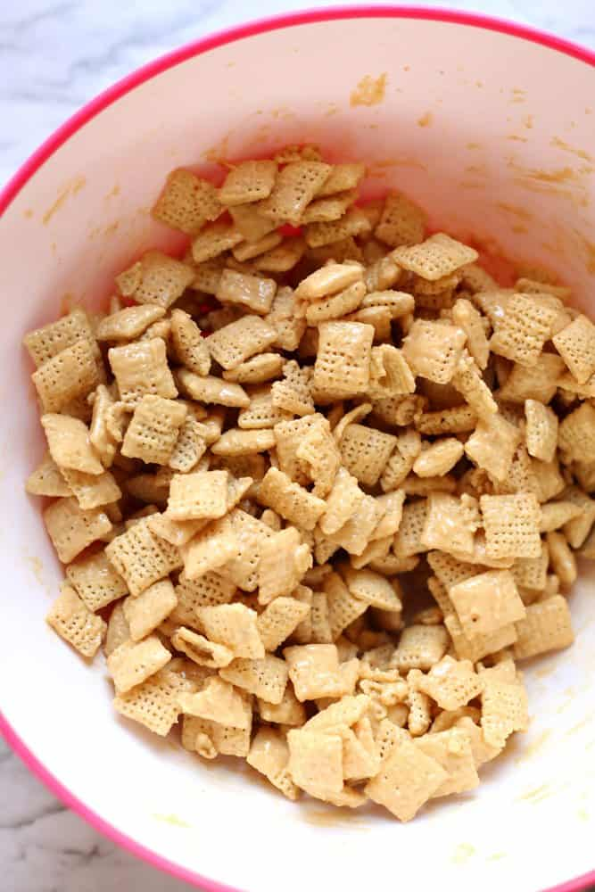 chex, peanut butter, white chocolate chips in a bowl stirred together