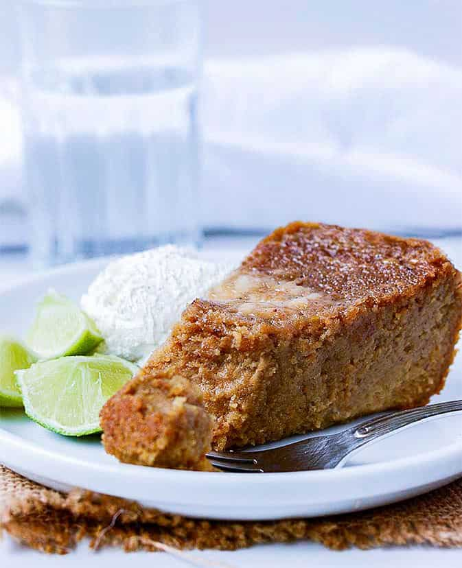 sweet potato pudding slice on white plate with lime slices