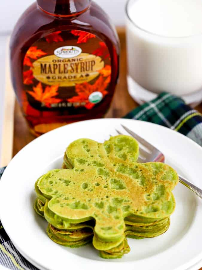 green shamrock shaped pancakes with maple syrup