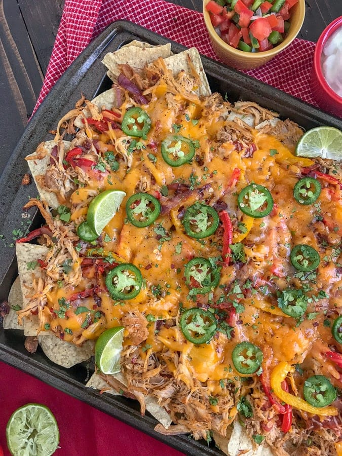 Loaded Chipotle Chicken Carnitas Nachos- more than likely the easiest, most flavor-packed nachos you will ever make! These nachos are loaded with chipotle chicken carnitas, salsa, cheese, sautéed onions and peppers, jalapeños, and topped with some amazing dips! #nachos #carnitas #loadnachos #mexican #tacotuesday #cincodemayo | https://withpeanutbutterontop.com