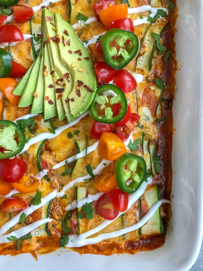 """Creamy, shredded chicken stuffed into zucchini """"rolls"""" and then baked in enchilada sauce and cheddar and monetary jack cheese. Very easy to make, low-carb, keto-friendly, and full of amazing flavors! #chickenenchiladas #lowcarb #keto #enchiladas 