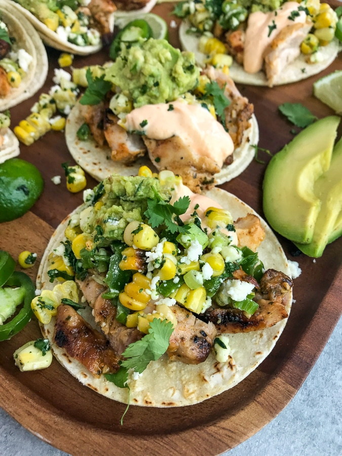 Easy, delicious grilled chicken tacos that are loaded with mexican street corn, mashed avocado, and creamy sriracha sauce!