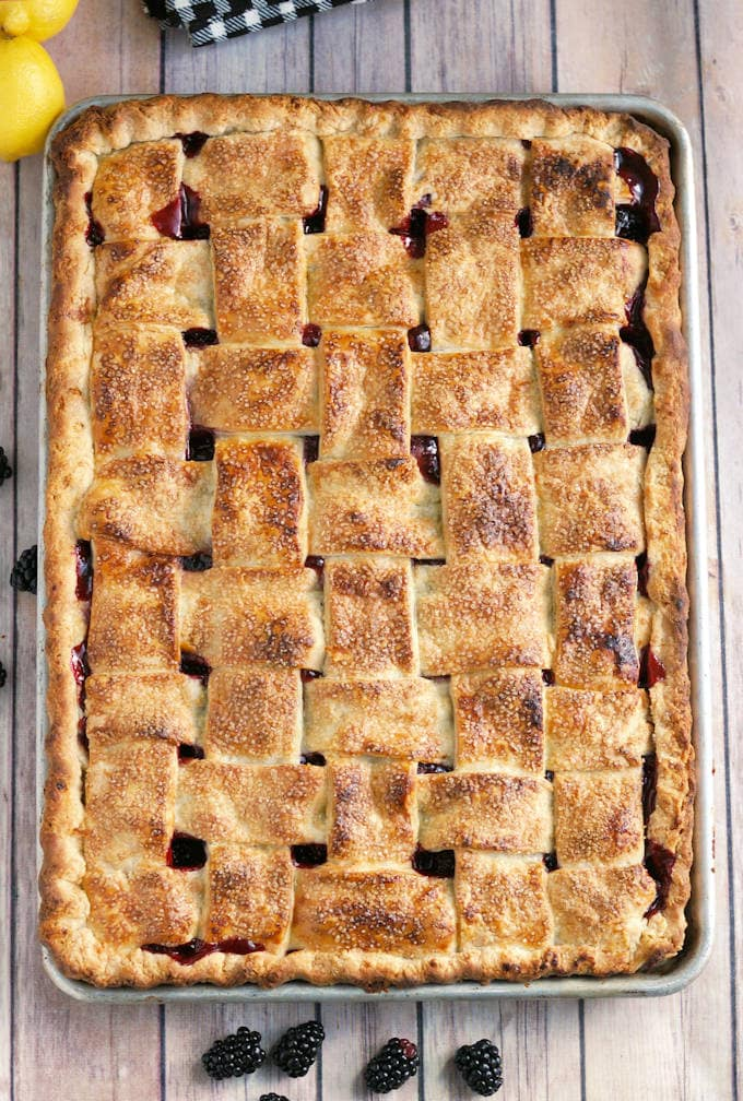 A half sheet pan pie with a lattice crust on a wooden table.