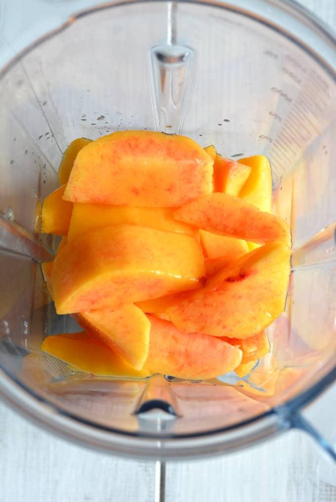 Fresh peaches inside a blender.