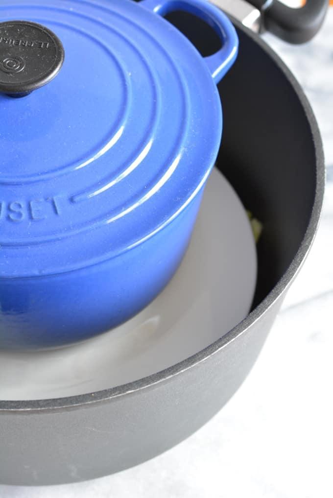 A blue pot on top of white plate inside a black larger pot.