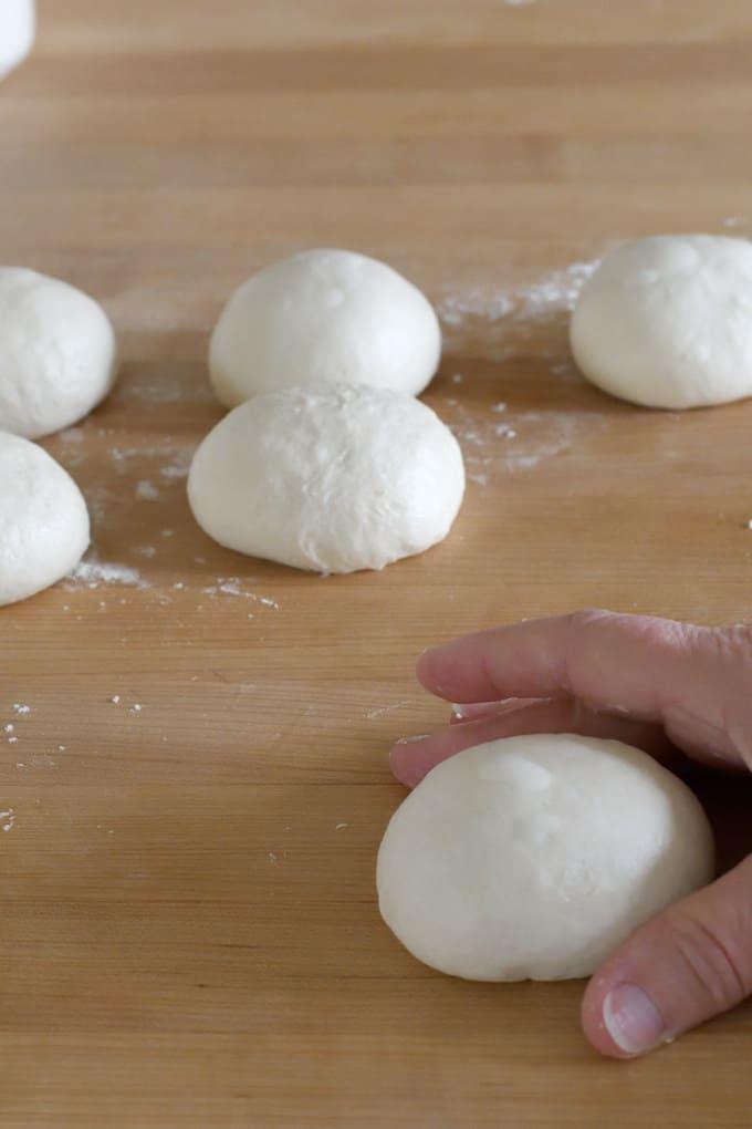 a hand shaping a piece of sourdough into a ball