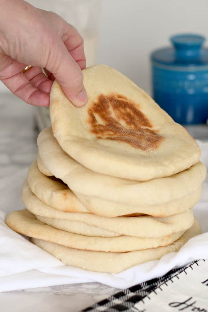a hand grabbing a pita bread from a stack