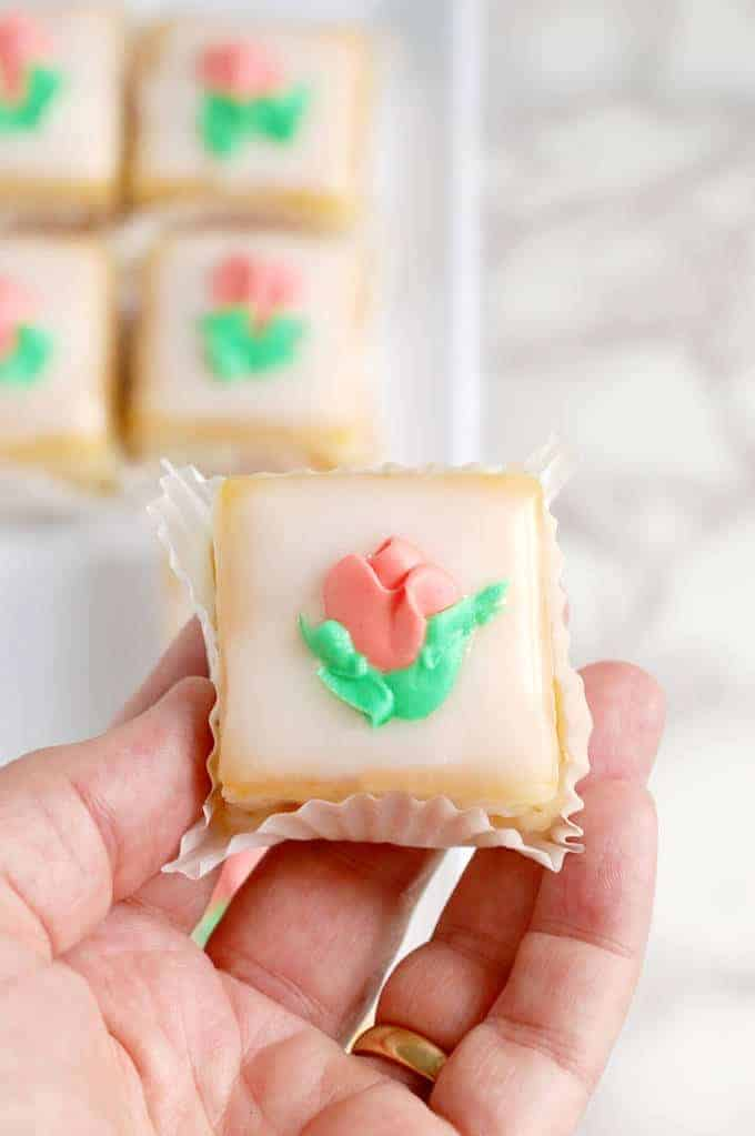 a hand holding a petit four with fondant icing