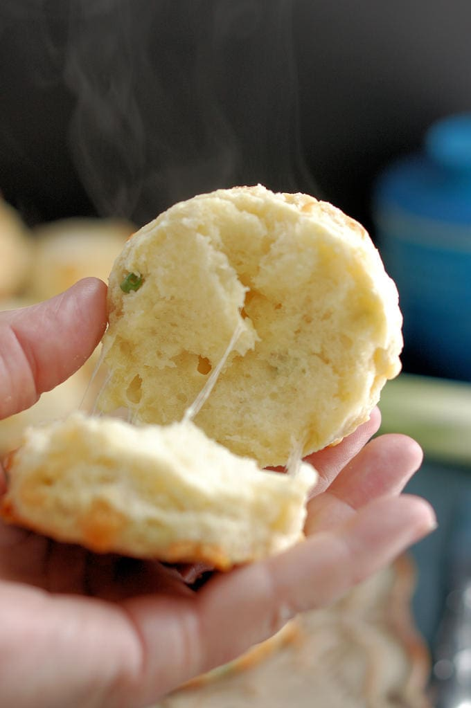 A closeup shot of a split cheese scone. You can see melting cheese and rising steam against the dark background.