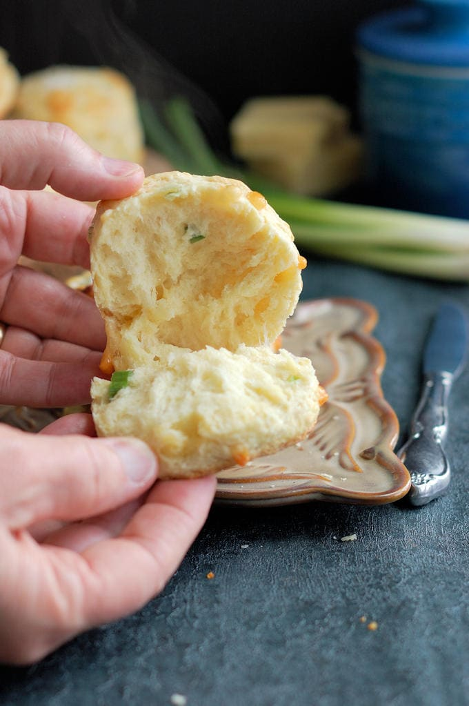 A closeup shot of a warm cheese scone opened up with melting cheese and steam against a dark background.