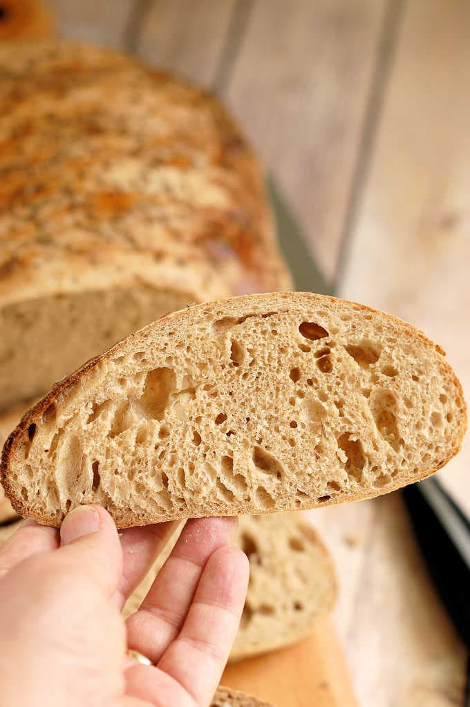 a hand holding a slice of sourdough rye bread