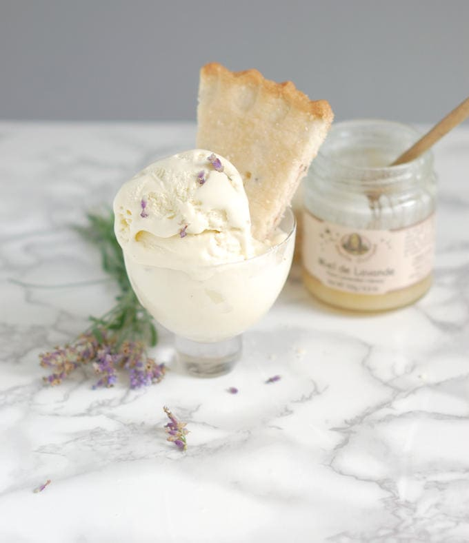 a bowl of lavender honey ice cream with a lavender honey shortbread cookie