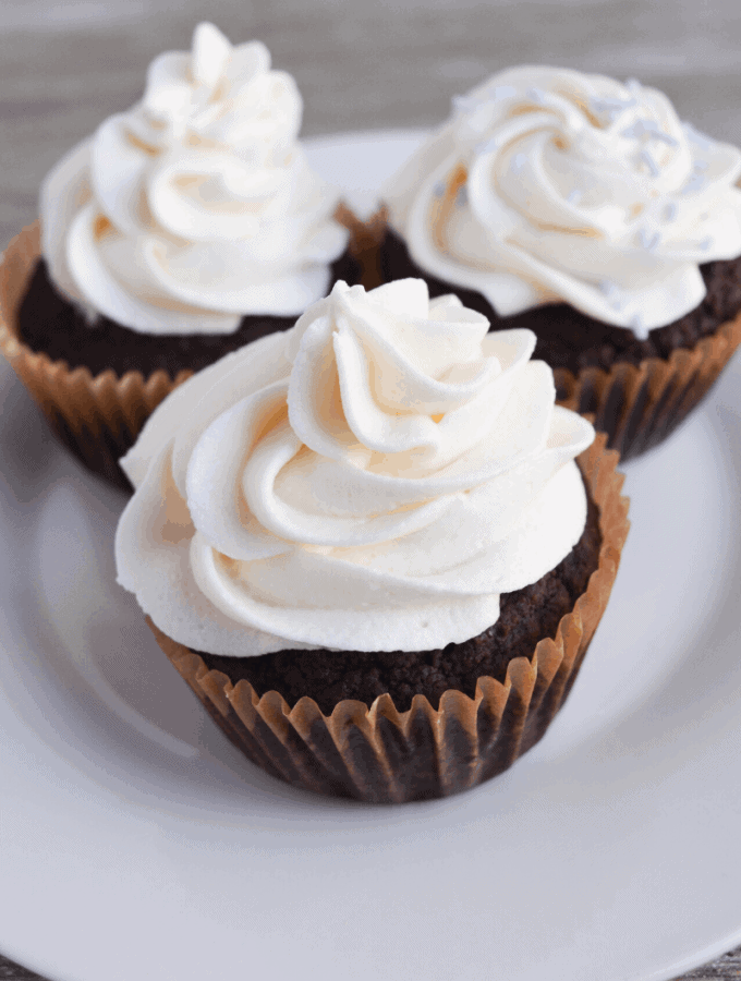 three chocolate cupcakes frosted with vanilla frosting sitting on a white plate
