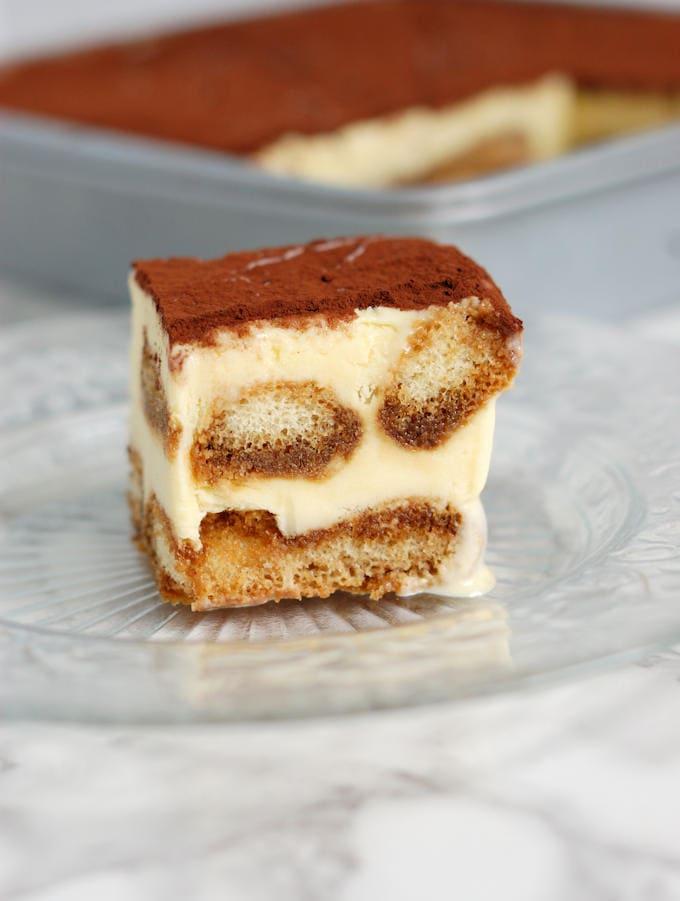 a slice of frozen tiramisu ice cream cake on a glass plate