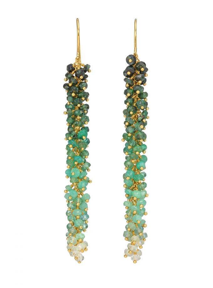 Photo of emerald earrings, with ombre effect, on gold china. White background.