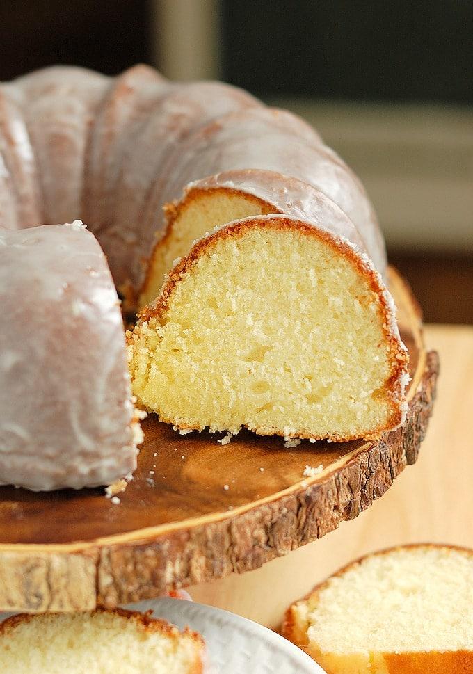 a sliced buttermilk bundt cake on a wood cake stand