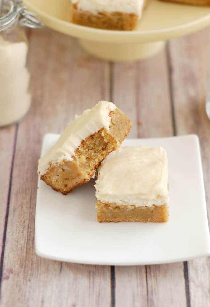 two frosted blondies on a white plate.
