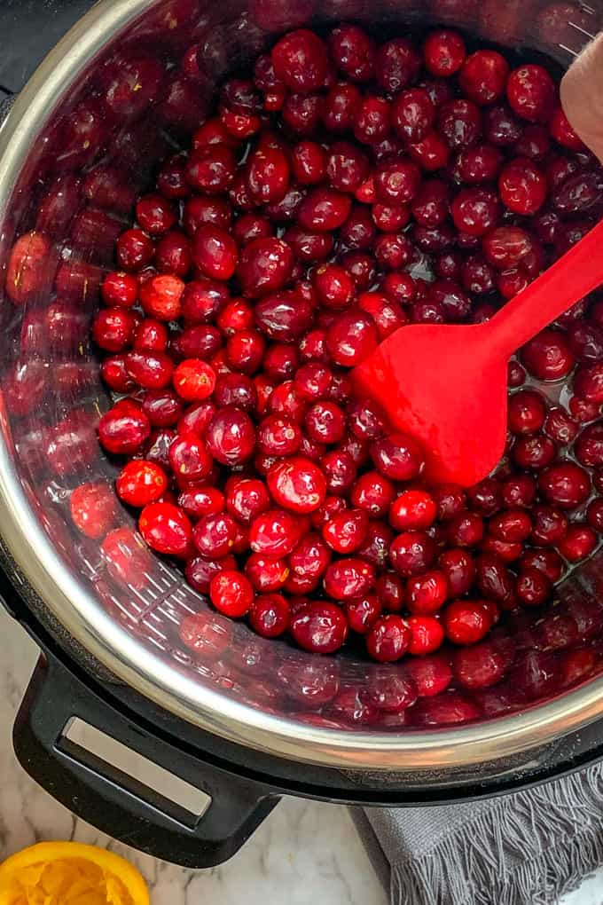Stir cranberries in the Instant Pot for making cranberry butter