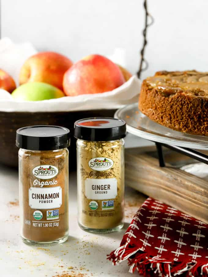 Sprouts farmers market spices cinnamon and ginger with apple basket in background and apple cake