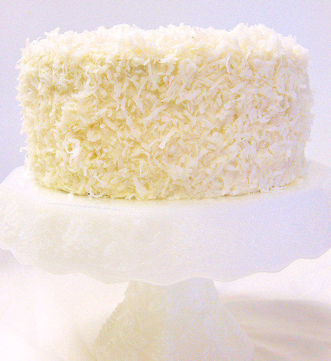 A coconut cake on a white cake stand