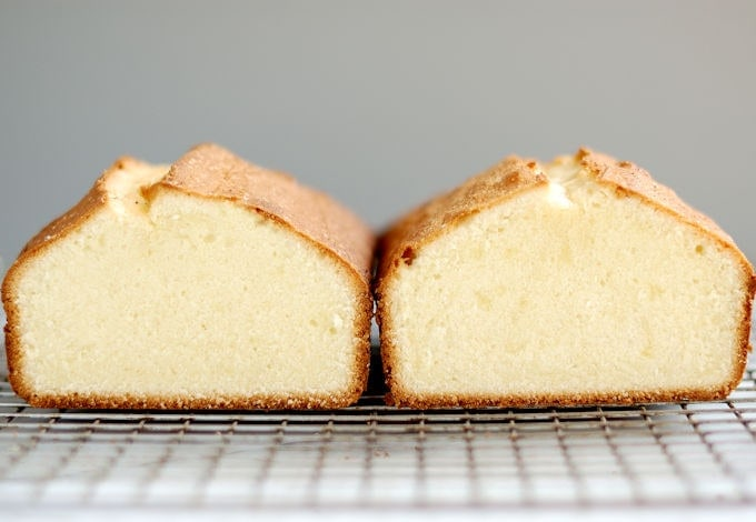 Two pound cakes side by side on a cooling rack with a gray background