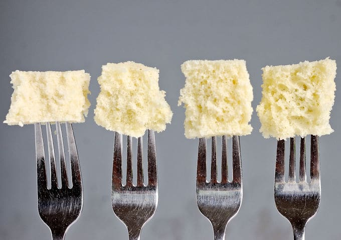 Four fork each with a bite of cake at the end against a gray background