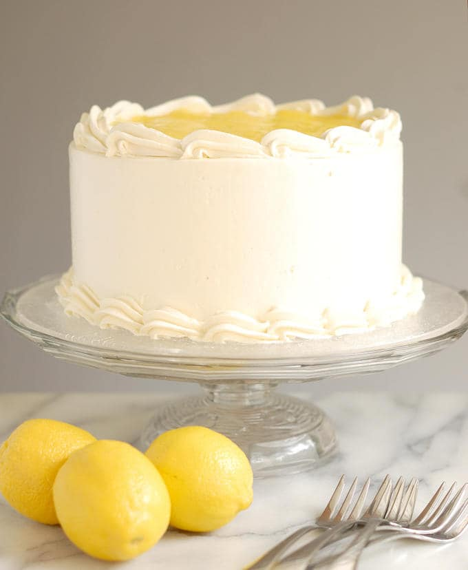 a lemon layer cake on a glass cake stand