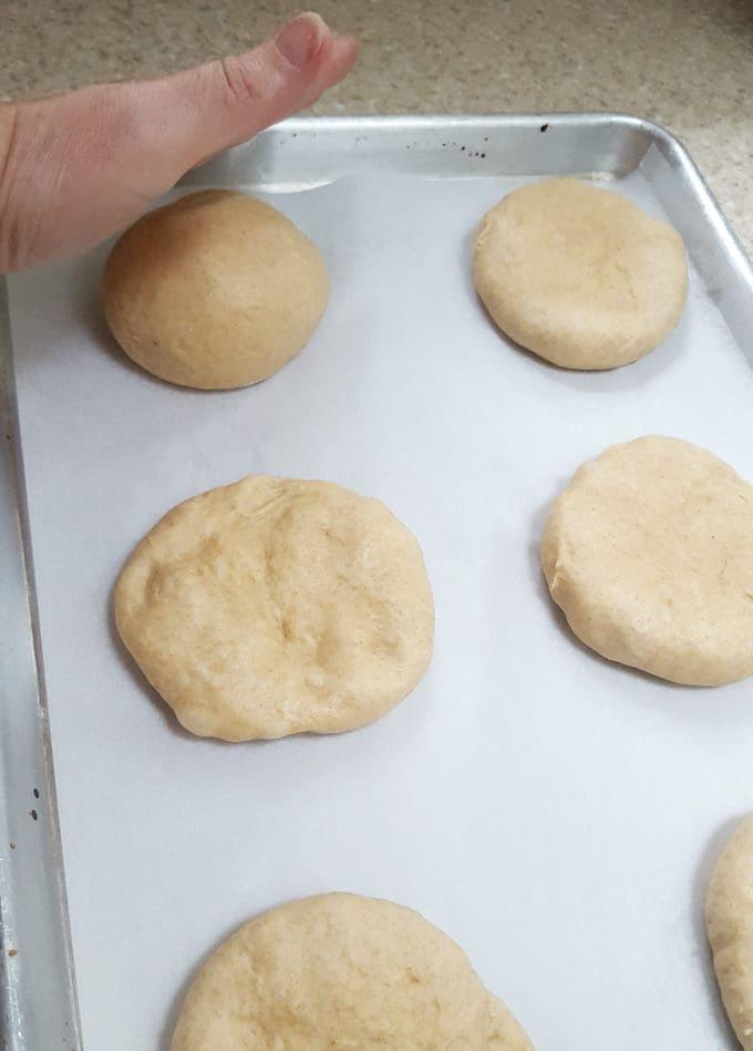 showing how to flatten dough for burger buns