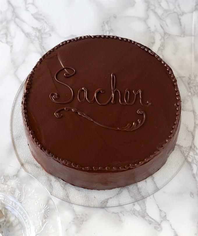 a sacher torte on a glass cake plate