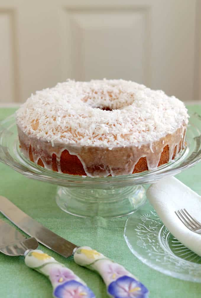 A coconut cake on a glass cake stand.