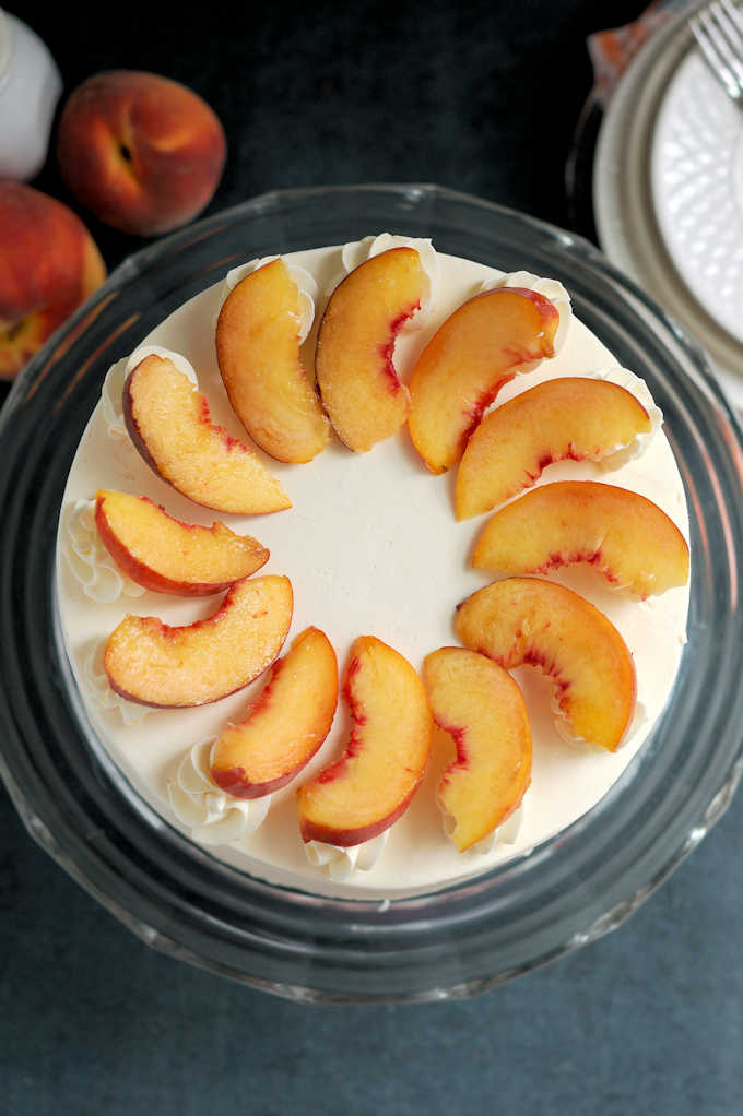 top view of a peach melba cake decorated with fresh peach slices