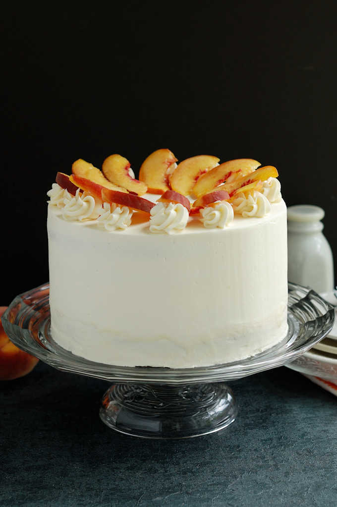 a peach melba cake on a glass cake stand against a black background
