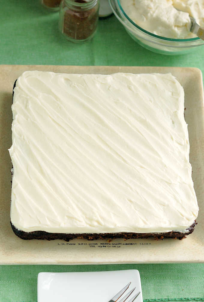 a square zucchini cake with cream cheese frosting on a square plate.