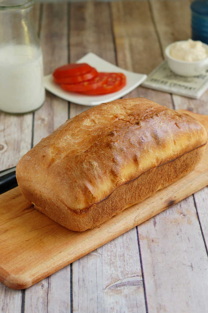 a loaf of sourdough sandwich bread on a cutting board