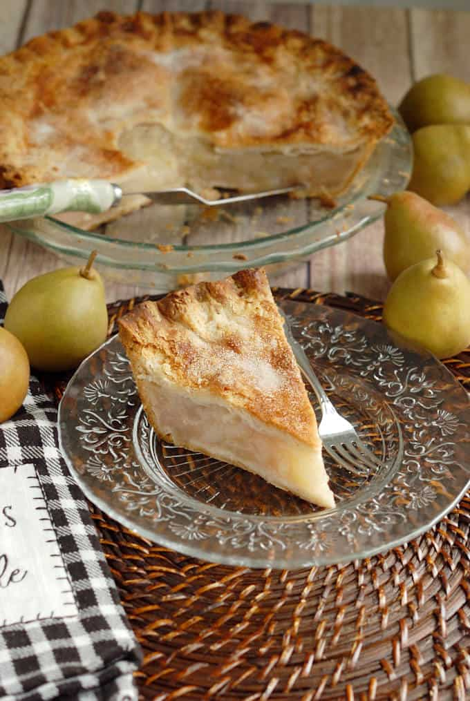 a slice of vanilla pear pie on a glass plate