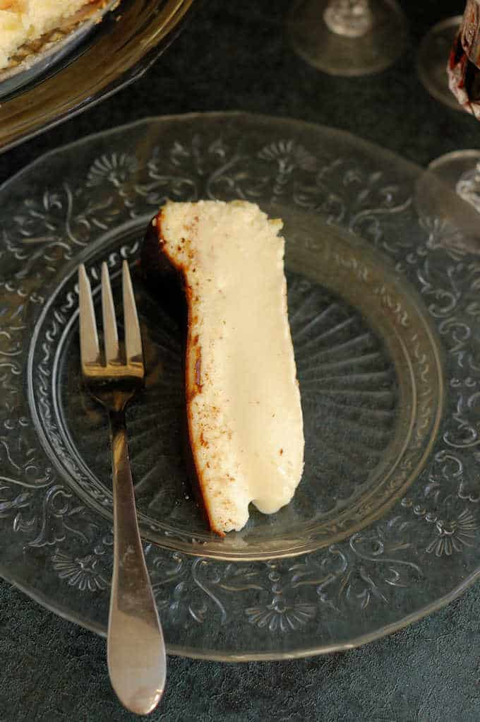 a slice of san sebastian cheesecake on a glass plate.