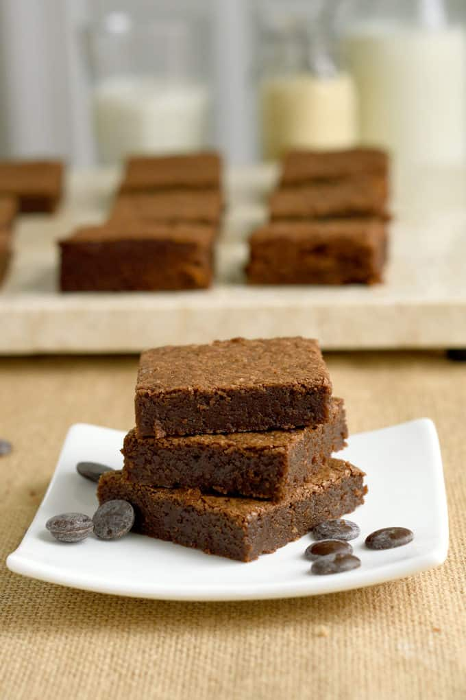 a stack of un-iced malted milk brownies on a plate