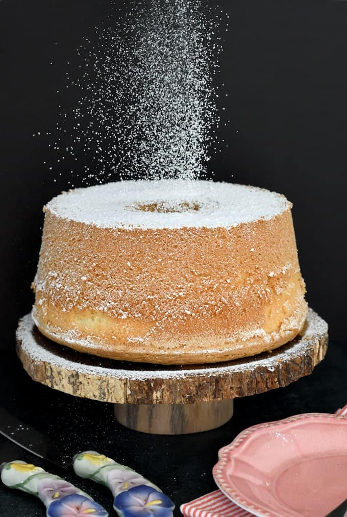 A vanilla chiffon cake on a cake stand being sprinkled with sugar