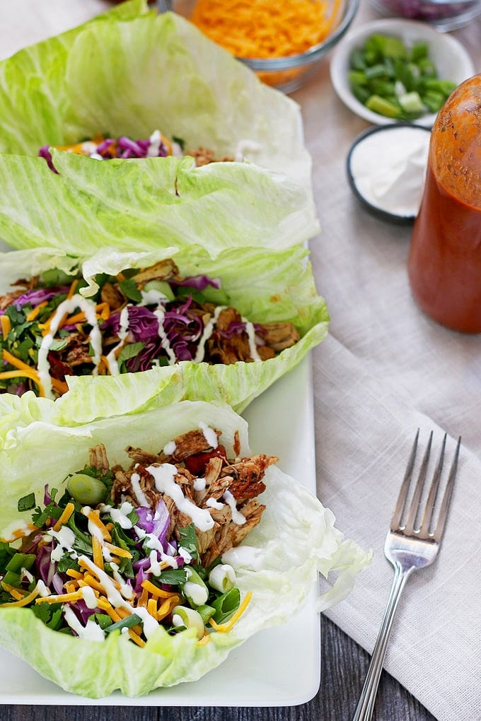 These slow cooker chicken taco lettuce wraps are going to be your new favorite taco recipe. Make the chicken taco meat in the slow cooker and substitute iceberg lettuce leaves for tortilla shells! | honeyandbirch.com