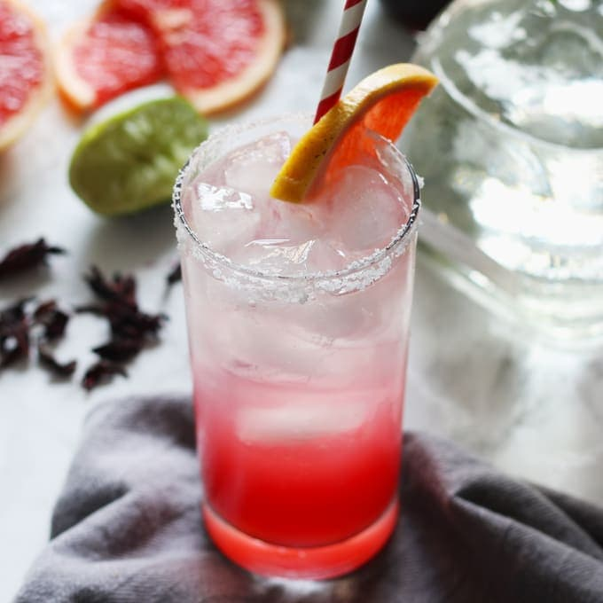 This hibiscus paloma cocktail is a refreshing recipe; the tart grapefruit and lime juices are well complemented by the sweet floral hibiscus simple syrup. Break out that bottle of tequila and mix up a batch of these drinks today! | honeyandbirch.com