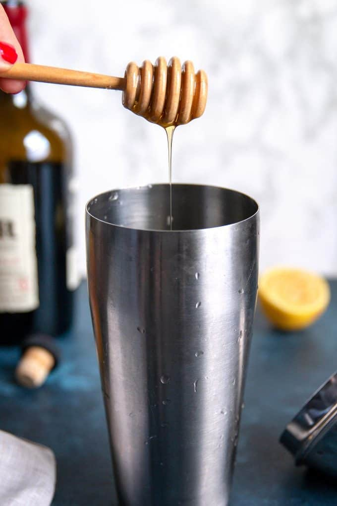 honey being dripped into a cocktail shaker