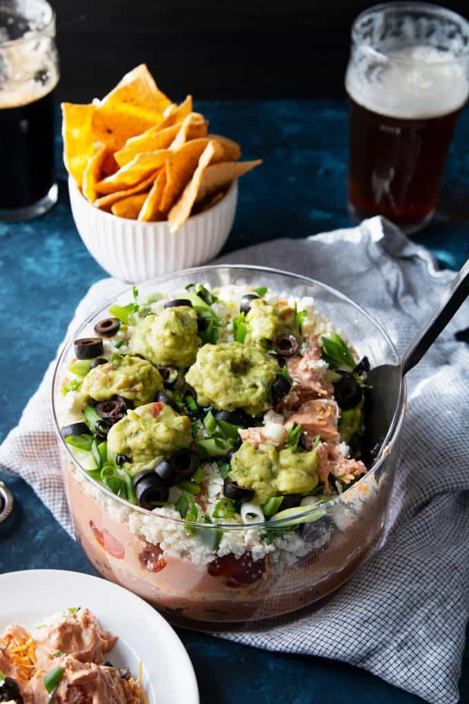 7 layer bean dip recipe with a large serving spoon