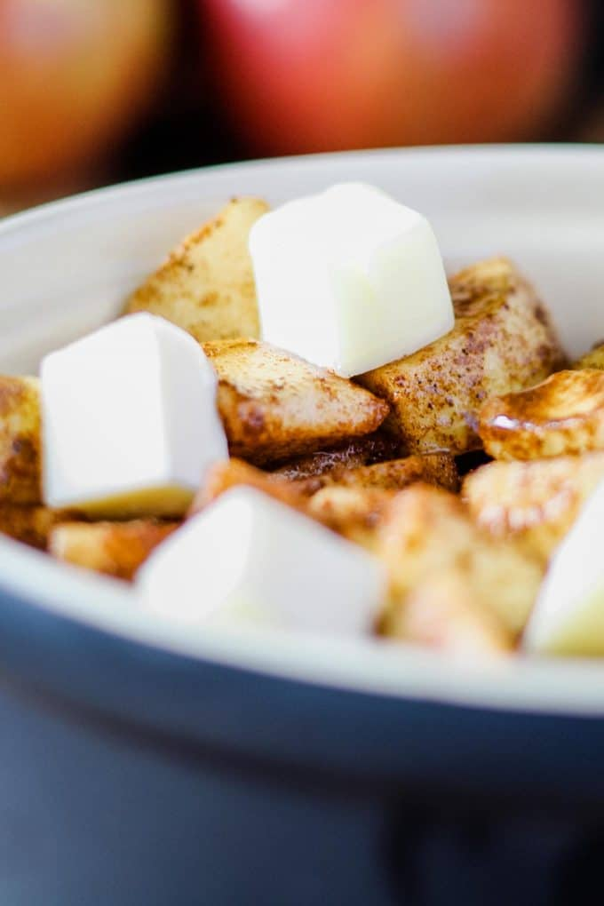 closeup of cut cubed butter on unbaked spiced apples