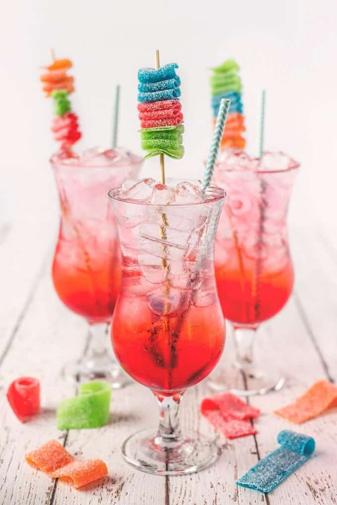3 shirley temple drinks in tall glasses on a white wooden table garnished with candy kabobs