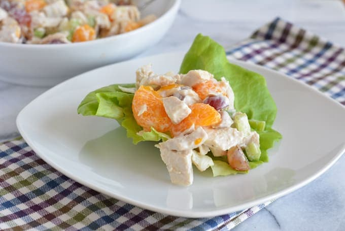 Chicken salad mixed with grapes and mandarin oranges on a white plate next to a white bowl with additional chicken salad.