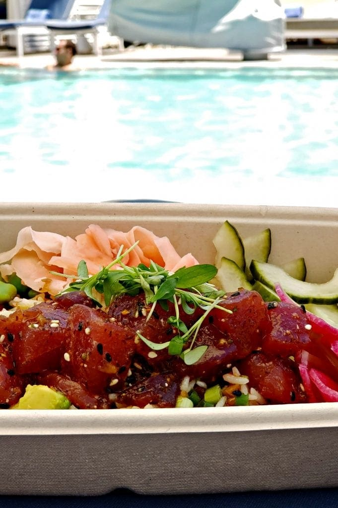 Poke bowl with ahi tuna, cucumber, radish sprouts and ginger in foreground - pool in background