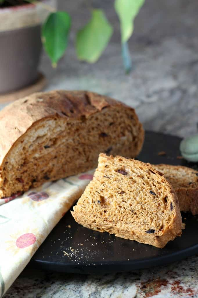 round loaf of sun dried tomato and olive bread sliced in half