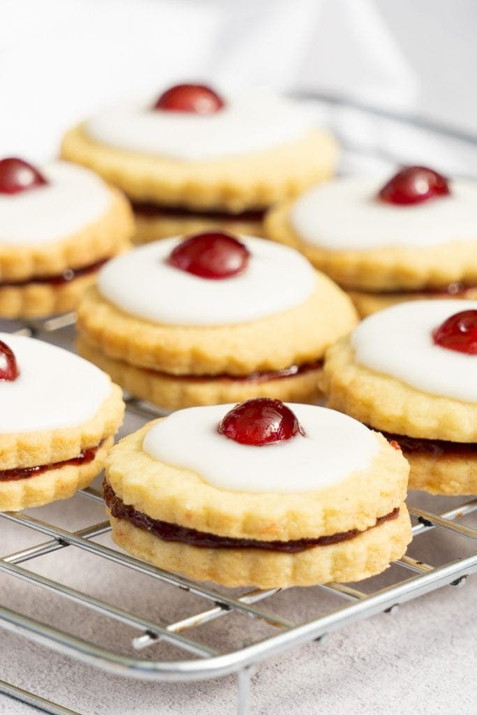 Scottish Empire Biscuits on a cooling rack - Shortbread with jam, icing, and a cherry on top